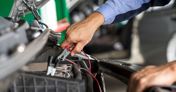 Professional car mechanic using jumper cables to start a car battery.